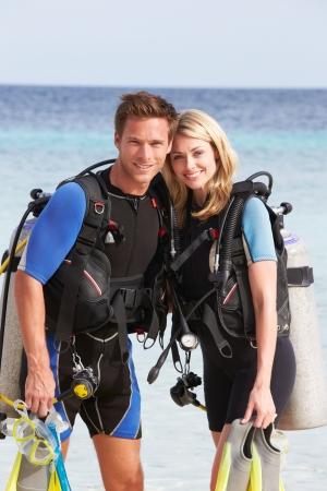 スキューバ ダイビング装備をビーチでの休暇を楽しむカップルします。