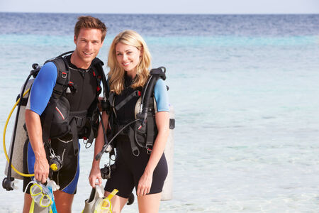 Couple With Scuba Diving Equipment Enjoying Beach Holiday photo