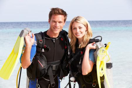 カップルはビーチでの休暇を楽しんでいるスキューバ ダイビング機器