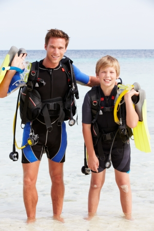 Father And Son With Scuba Diving Equipment On Beach Holiday photo