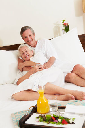 Senior Couple Relaxing In Hotel Room Wearing Robes Stock Photo - 24492469