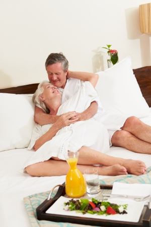 Senior Couple Relaxing In Hotel Room Wearing Robes photo