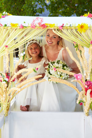 Bride And Bridesmaid Sitting Under Decorated Canopy photo