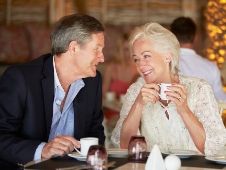 Senior Couple Enjoying Cup Of Coffee In Restaurant photo
