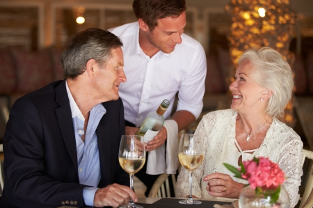 couple dining: Waiter Serving Wine To Senior Couple In Restaurant