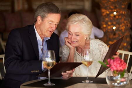 Senior Couple Choosing From Menu In Restaurant photo
