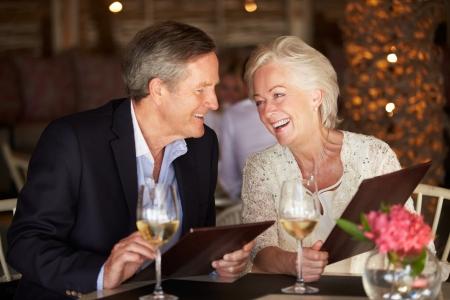 dining tables: Senior Couple Choosing From Menu In Restaurant