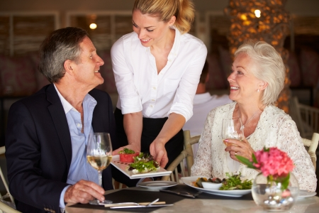 couple dining: Waitress Serving Food To Senior Couple In Restaurant