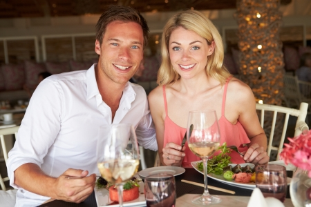 Couple Enjoying Meal In Restaurant photo