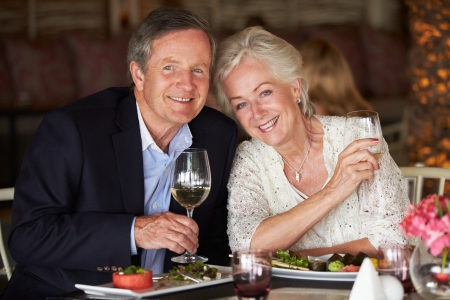 mealtime: Senior Couple Enjoying Meal In Restaurant Stock Photo