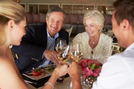 bebiendo vino: Grupo de amigos que disfrutan de la comida en restaurante Foto de archivo