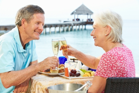 Senior Couple Enjoying Meal In Seafront Restaurant photo