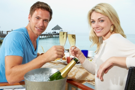 Couple Enjoying Meal In Seafront Restaurant photo