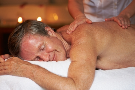 therapist: Senior Man Having Massage In Spa Stock Photo