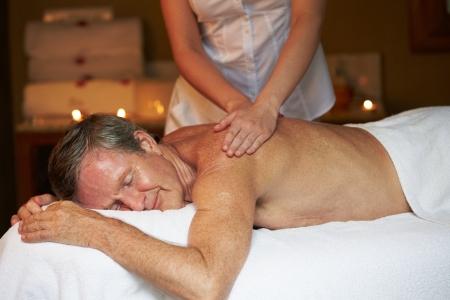 homme massage: Homme aîné ayant un massage au spa Banque d'images
