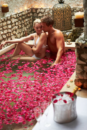 loving: Couple Relaxing In Flower Petal Covered Pool At Spa