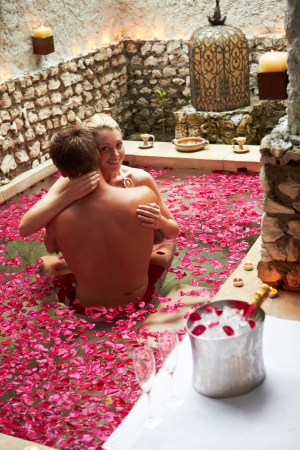 Couple Relaxing In Flower Petal Covered Pool At Spa photo