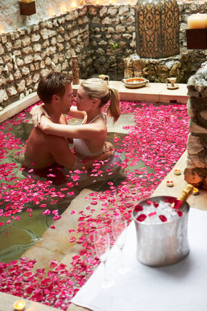 Couple Relaxing In Flower Petal Covered Pool At Spa Stock Photo - 24493503