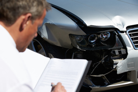 adjuster: Loss Adjuster Inspecting Car Involved In Accident Stock Photo