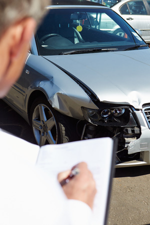 Loss Adjuster Inspecting Car Involved In Accident Stock Photo