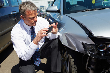 accident damage: Loss Adjuster Inspecting Car Involved In Accident Stock Photo