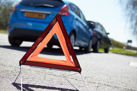 danger of accident: Warning Triangle By Two Cars Involved In Accident