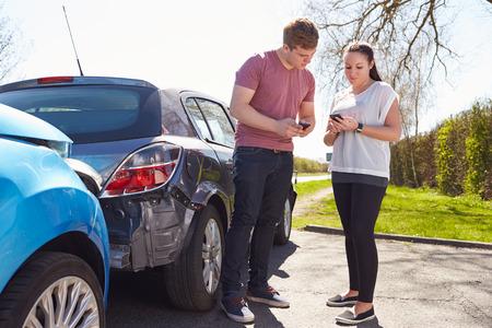 2 つのドライバーは、事故後保険の詳細を交換します。