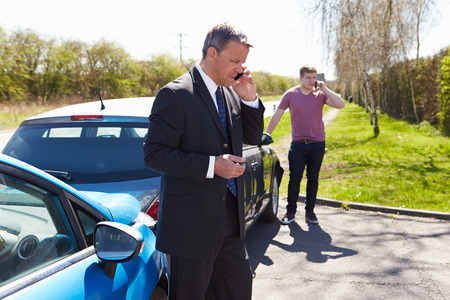 accident damage: Businessman Making Phone Call After Traffic Accident Stock Photo