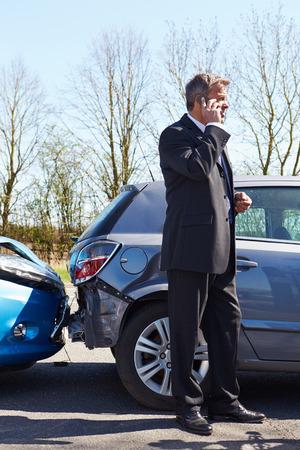 交通事故後の電話を作るビジネスマン