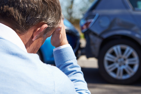 Stressed Driver Sitting At Roadside After Traffic Accident photo