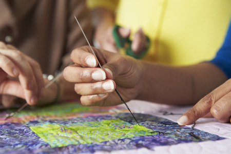 女性の手の縫製キルトのクローズ アップ