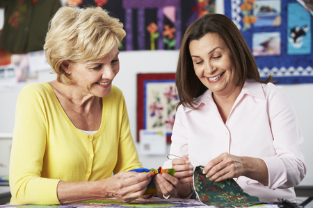 2 人の女性が一緒にキルトを縫う