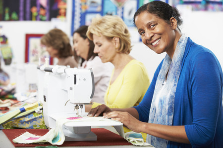 sewing needle: Group Of Women Using Electric Sewing Machines In class Stock Photo
