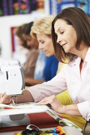 stitching machine: Group Of Women Using Electric Sewing Machines In class Stock Photo