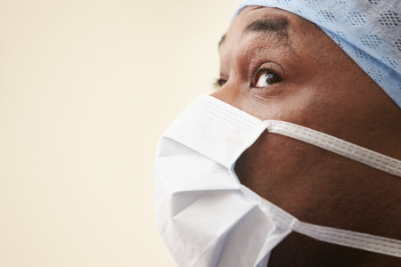 Surgeon In Operating Theatre Wearing Scrubs And Mask photo