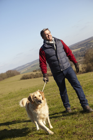 dog leash: Man Taking Dog On Walk In Autumn Countryside
