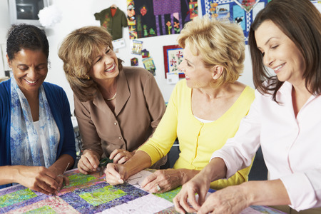 patchwork quilt: Group Of Women Making Quilt Together