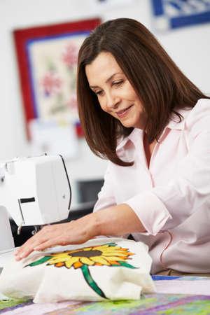 Woman Using Electric Sewing Machine photo