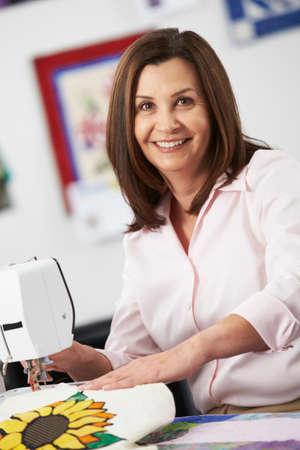 stitching machine: Portrait Of Woman Using Electric Sewing Machine Stock Photo
