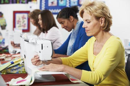 Group Of Women Using Electric Sewing Machines In class Фото со стока