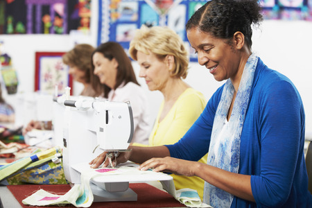 Group Of Women Using Electric Sewing Machines In class photo