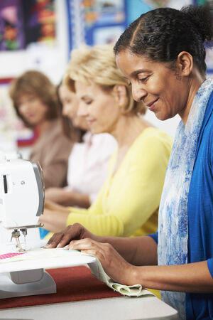 sewing machines: Group Of Women Using Electric Sewing Machines In class Stock Photo