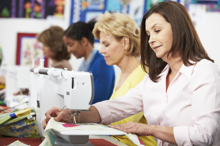 Group Of Women Using Electric Sewing Machines In class Stockfoto
