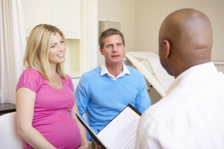 40s adult: Couple Meeting With Obstetrician In Clinic