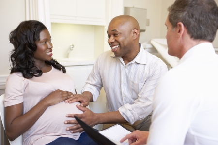 black pregnant woman: Couple Meeting With Obstetrician In Clinic