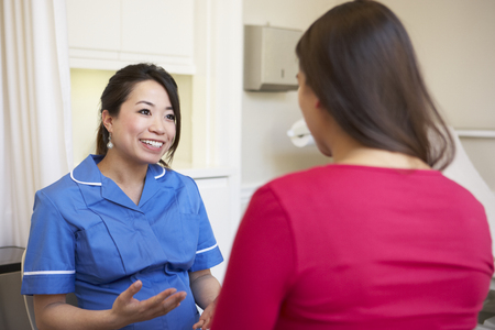 asian nurse: Pregnant Woman Meeting With Nurse In Clinic Stock Photo