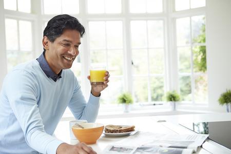 eating breakfast: Indian Man Enjoying Breakfast At Home Stock Photo