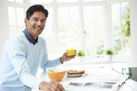 Indian Man Enjoying Breakfast At Home Banco de Imagens