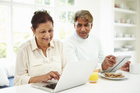 Senior Indian Couple Using Laptop And Digital Tablet At Home photo
