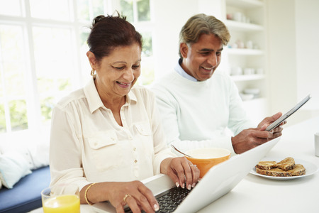 senior eating: Senior Indian Couple Using Laptop And Digital Tablet At Home